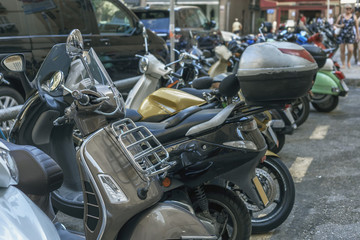 motorcycles and mopeds in the street Parking on a Sunny summer day