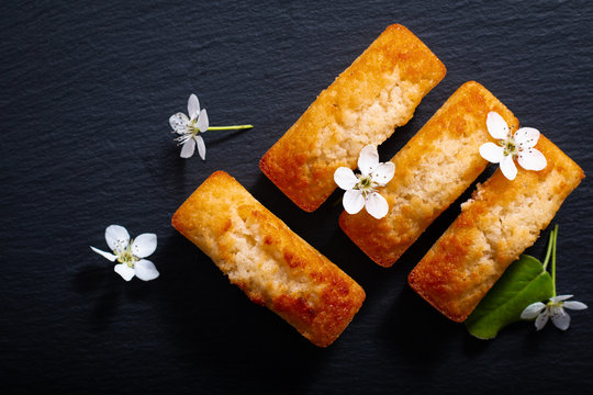 Food concept mini French almond cake financier on black slate stone with copy space