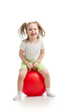 happy child girl jumping on bouncing ball. Isolated on white.