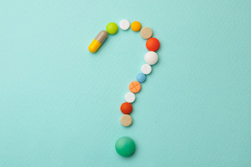 Symbol question mark from colored tablets and capsules on  green background. What medicines to choose better, what will help