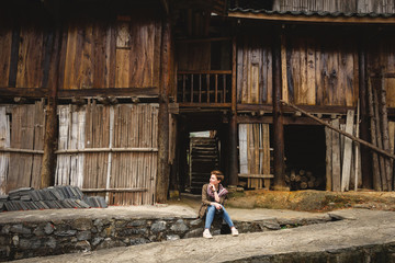 Pretty girl enjoys holidays in the village with wooden houses
