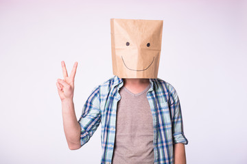 Unknown man showing victory sign with a paper bag on his head on white background