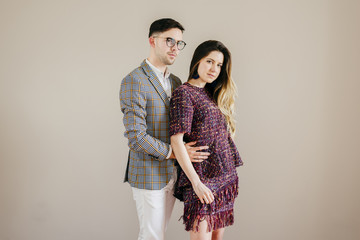 Fashionable couple at beige wall
