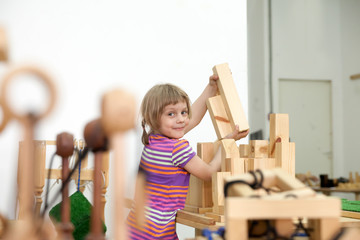 girl playing in wooden puzzles.