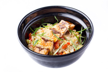 Japanese food. Rice with vegetables and fried salmon in a black bowl. Japanese food dish isolated on white background.