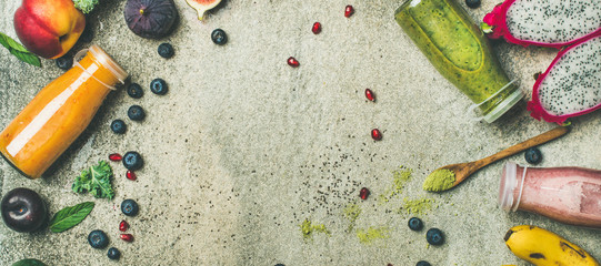 Colorful smoothies in bottles with fresh tropical fruit and superfoods on grey concrete background, top view, copy space. Healthy, vegetarian, detox, dieting, clean eating breakfast food concept