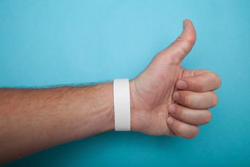 Empty event ticket wrist band design. White blank paper wristband, bracelet mockup on blue background.