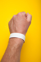 Man hand with round wristband for an event bracelet on the arm, mockup.