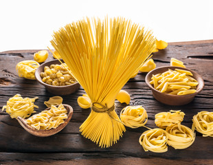 Different pasta types on wooden table. White background.