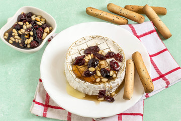 Baked brie cheese with dried cranberries and nuts sauce