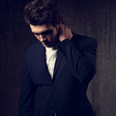 Thinking serious handsome business man looking down in black fashion suit and white style shirt on dark shadow background. Art. Toned closeup portrait