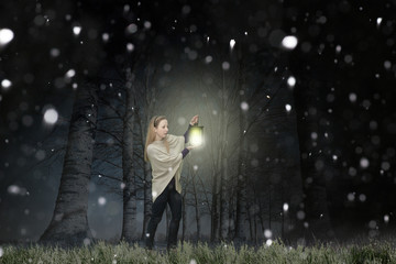 Woman with lantern in the forest