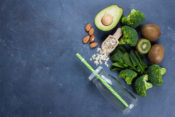 Ingredients for Healthy Green Smoothie. Broccoli, avocado, spinach, kiwi, oats and almond on blue concrete stone table background. Vegetarian Food Concept. Top view, copy space