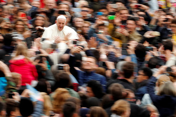 Pope Francis waves as he arrives to lead the Wednesday general audience in Saint Peter's square at the Vatican