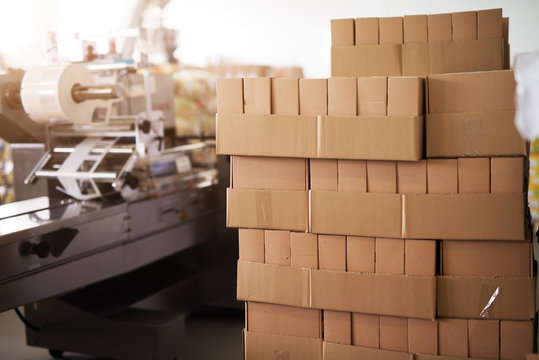 Big stack of brown boxes placed near the factory production line.
