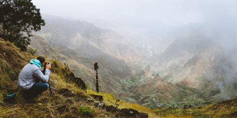 Panoramic shot of traveler making photo of amazing steep mountainous terrain with lush canyon valley on the path from Xo-Xo Valley. Cloudy sky. Santo Antao Island, Cape Verde
