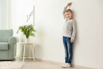 Cute little boy measuring height near wall at home