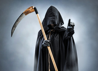 Grim Reaper points at you. Photo of personification of death wielding a large scythe in silhouette.