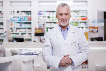 Come in. Mature joyful male pharmacist looking at camera while grinning