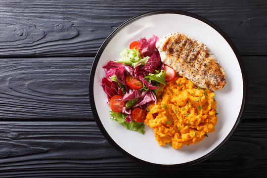 Delicious grilled chicken with garnish of sweet potato and fresh salad close-up on a plate. horizontal top view