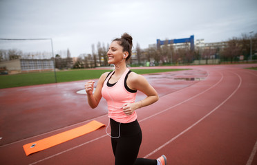 Side view of attractive shape young happy fitness girl jogging while listening to music outside near the soccer field.