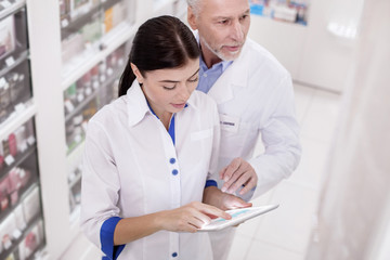 Mutual help. Top view of thoughtful two pharmacists standing while using tablet