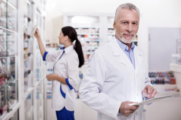 Responsibility for health. Jolly male pharmacist using tablet while grinning to camera