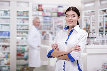Working morning. Happy female pharmacist staring at camera while crossing arms