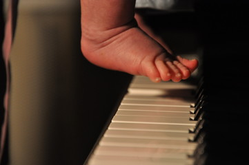 The child's foot presses the piano keys