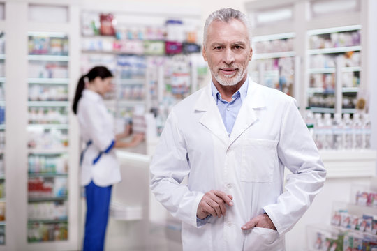 Perfect drugstore. Senior ambitious male pharmacist putting hand in pocket while looking at camera