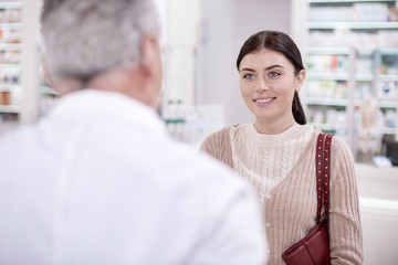 Help me. Cheerful female client smiling while talking to pharmacist