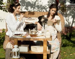 Two young women having tea outdoors
