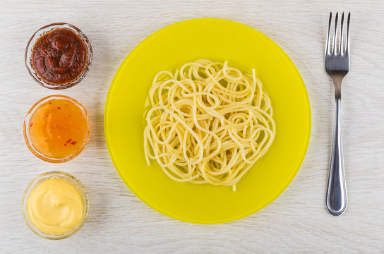Spaghetti in yellow plate, bowls with ketchup, mayonnaise and fork