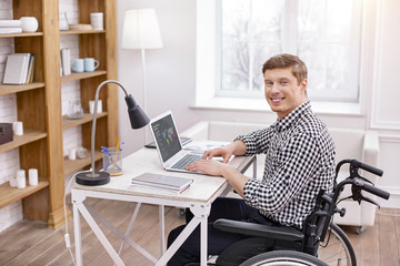 Follow my example. Cheerful IT man sitting in semi position while looking at camera