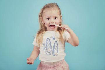 niña pequeña con cepillo de dientes sobre fondo azul