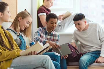 Group of multicultural high school teenage high school students doing homework during school break
