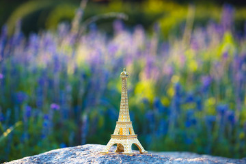 bright image of a miniaturized eiffel tower with lavander fields in background in day .