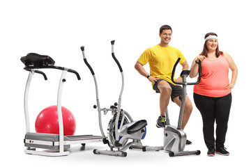 Young man and an overweight woman with exercise machines