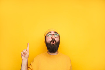 Interested hipster pointing up on yellow