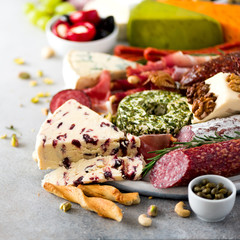 Traditional italian antipasto, cutting board with salami, cold smoked meat, prosciutto, ham, cheeses, olives, capers on grey background. Cheese and meat appetizer. Square crop
