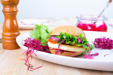 Homemade halloumi burger with lettuce, tomato, pickled red onion and beet sprouts. Gluten free bread.