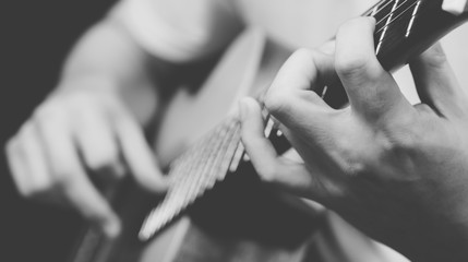 male musician playing acoustic guitar, black and white