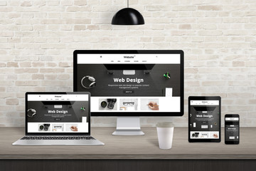 Responsive web site presentation on diferent display devices. Modern studio interior. Brick wall in background.