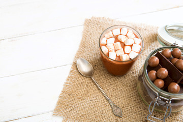 Chocolate milkshake with marshmallows on white wooden table