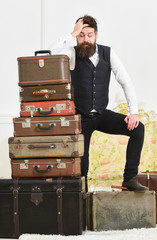 Macho elegant on disappointed face standing near pile of vintage suitcase. Luggage and travelling concept. Man, butler with beard and mustache delivers luggage, luxury white interior background.