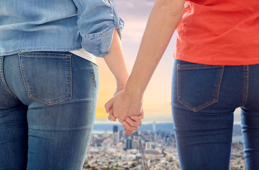 gay, same-sex marriage and homosexual relationships concept - close up of happy lesbian couple holding hands over san francisco city view background
