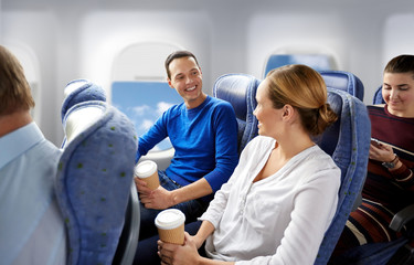 transport, tourism and air flights concept - happy passengers or tourists with coffee talking in plane over porthole background Wall mural