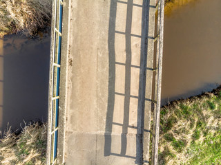Aerial view from a low height of 10 meters from a small bridge over a dark stream
