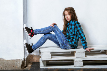 Female teenager sits on pallets near white concrete wall. Girl hipster child in bright blue shirt in a cage,jeans,sneakers.Fashion pose,legs on the wall. Caucasian adolescent in casual clothes.