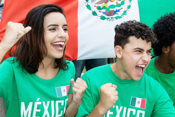 Young soccer fans from Mexico with mexican flag